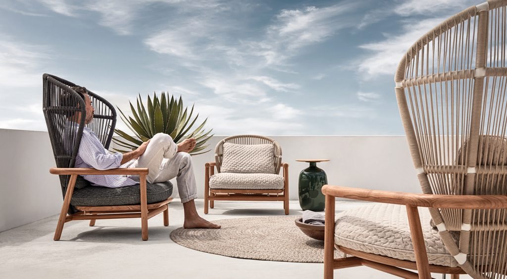 CHAPLINS Fern Collection by Gloster. Inspired by the delicate fronds of an unfurling leaf, the Fern Chair by Sebastian Herkner is a stately yet cosy outdoor lounge chair. Harnessing natural materials such as teak and rope, it creates the impression that one is being enveloped by Mother Nature herself.