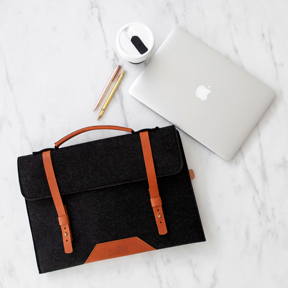 This luxury grey felt laptop bag has a sturdy leather handle and leather accessories, including a mobile phone pocket and room for documents, notebook, pens, cables, business cards, memory sticks, keys and sunglasses.