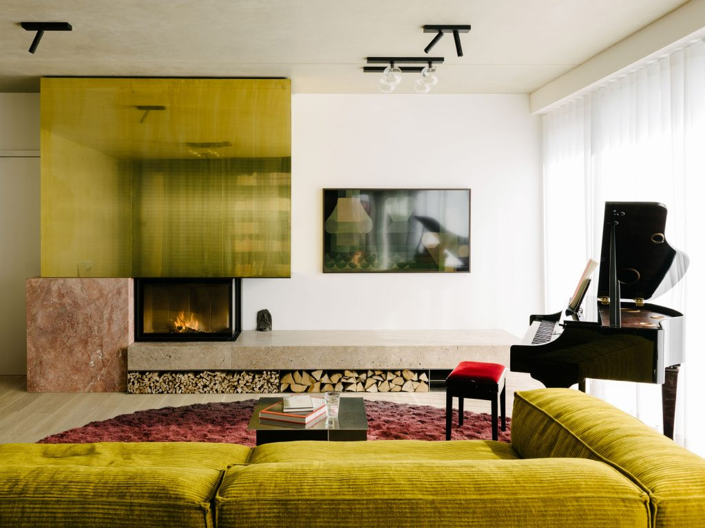 The Living Room occupies the space between an existing wall and the green box. The hearth is made from travertine Sierra ebru stone, red travertine, brass, and thin plates of stainless steel. Te design strategy is to create relationship between boxes. Photo ©Robert Rieger, Courtesy of Ester Bruzkus Architekten.