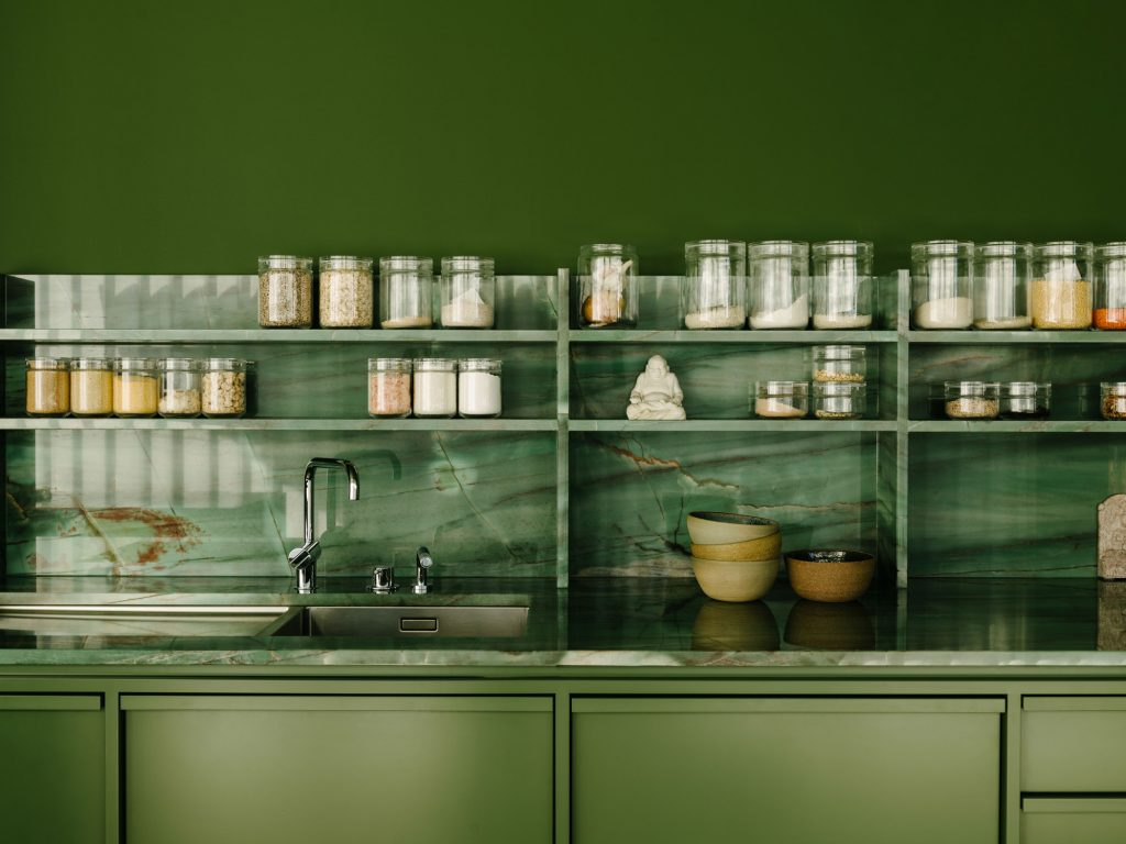 The kitchen counter, back and shelving are made from natural greenand- violet quartzite. The millwork on the green box is lacquered wood, some of which is detailed to have a strong rhythm of ribs. Photo ©Robert Rieger, Courtesy of Ester Bruzkus Architekten.
