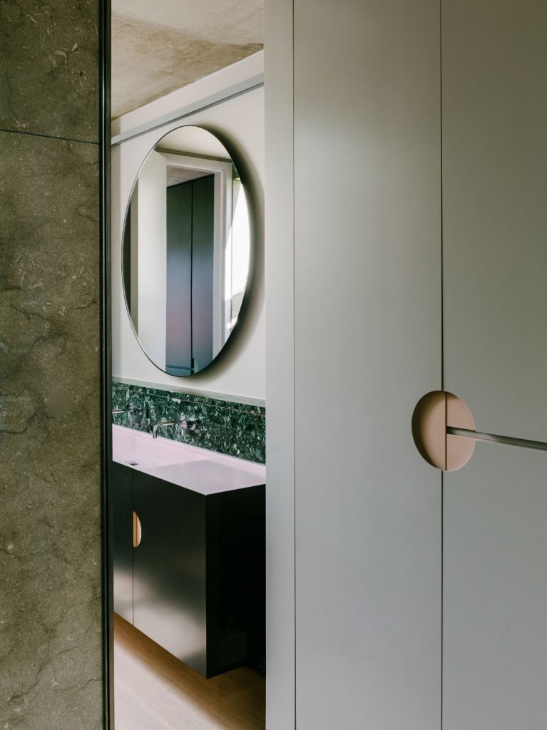 The bathroom occupies the space between the green box and the existing wall. Sinks are made from green marbles, black steel and pink basins; the shower and bathtub are made from a pale limestone that harmonizes with the other tones. The design also uses the simple geometry of the circle in a number of ways: in the design of handles for the cabinetry, in an oversized round mirror, and in a circular skylight that was built above the shower. All of the materials are brought together with the careful detailing that characterizes the work of Ester Bruzkus Architekten.