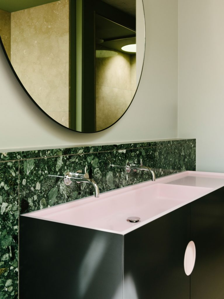 The bathroom sinks are made from green marble, black steel door fronts and pink CORIAN basins.