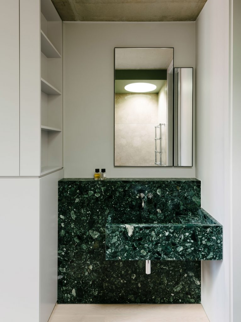 The guest sink is a composition of green marble. In the mirror, one can see a circular skylight that was built above the shower in the ceiling of the green box.