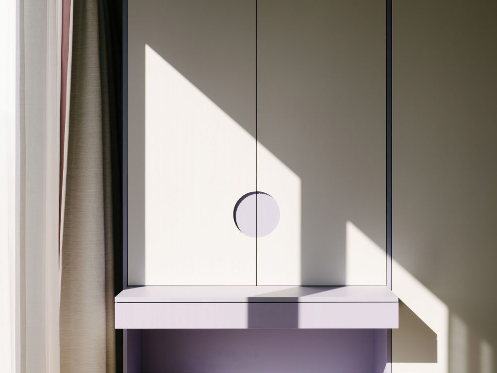 BEDROOM - A violet and gray desk that is built into the cabinetry. The large circle is the handle to the cabinet that recalls a similar detail in the bathroom. Photo ©Robert Rieger, Courtesy of Ester Bruzkus Architekten.