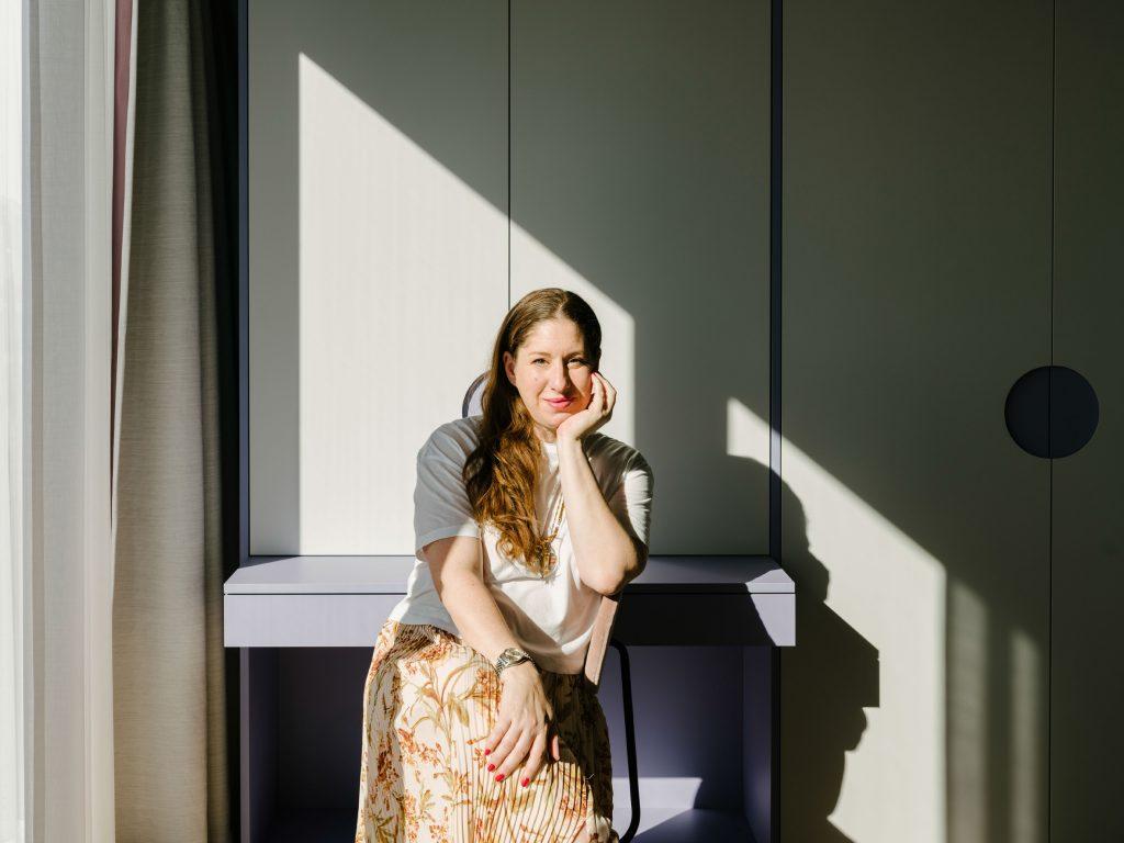 Ester Bruzkus poses at the violet table in the Green Box. Photo ©Robert Rieger, Courtesy of Ester Bruzkus Architekten.